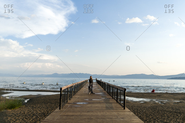 Woman with dog standing on pier against sky