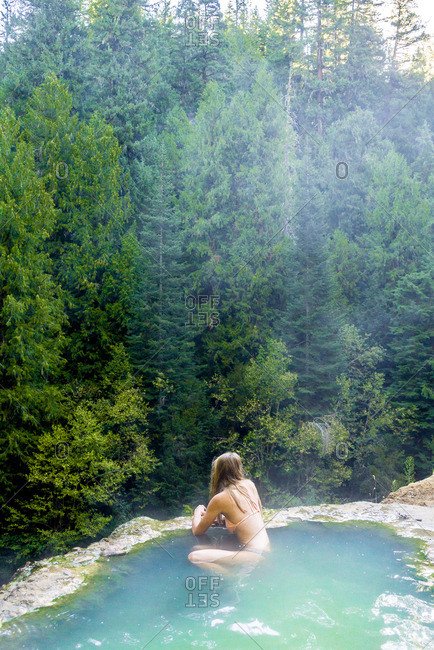 High angle view of woman swimming in hot spring at forest