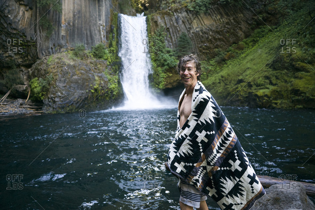 Portrait of happy man in shawl standing by waterfall in forest