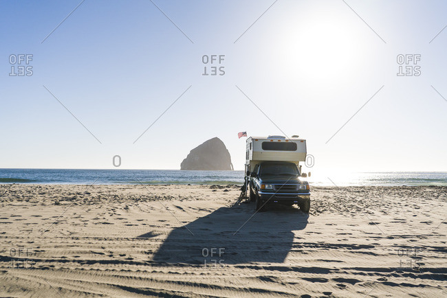Truck camper at beach against clear sky on sunny day