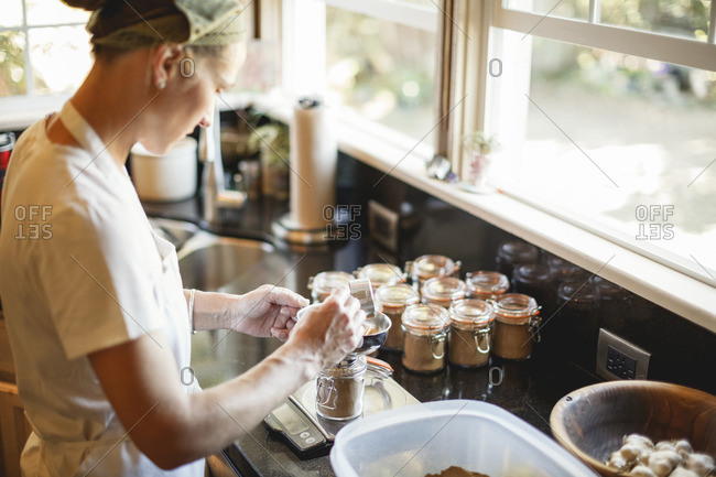 Woman filling spice in mason jars while standing at kitchen counter