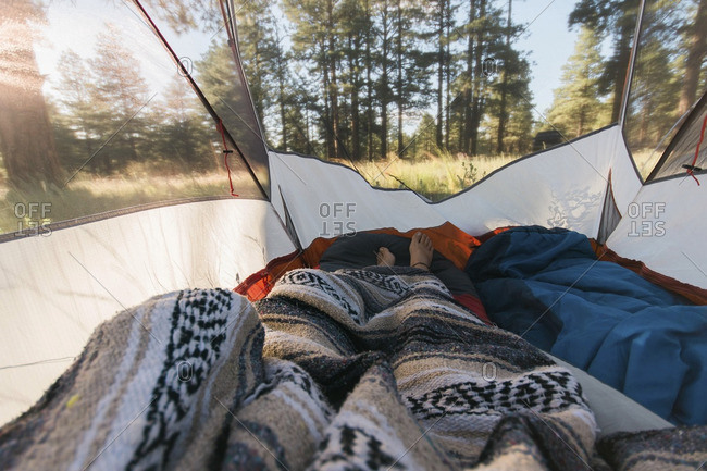 Low section of person wrapped in blanket lying inside tent at forest
