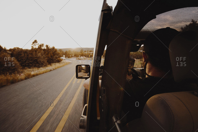 Rear view of man driving off-road vehicle window while driving on country road