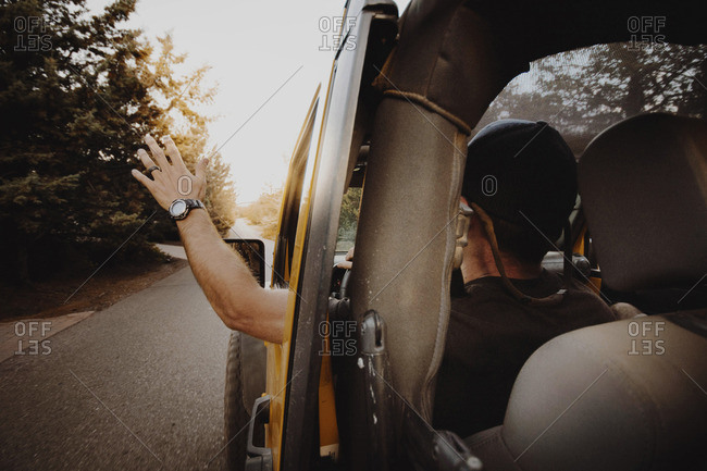 Rear view of man waving through off-road vehicle window while driving on road