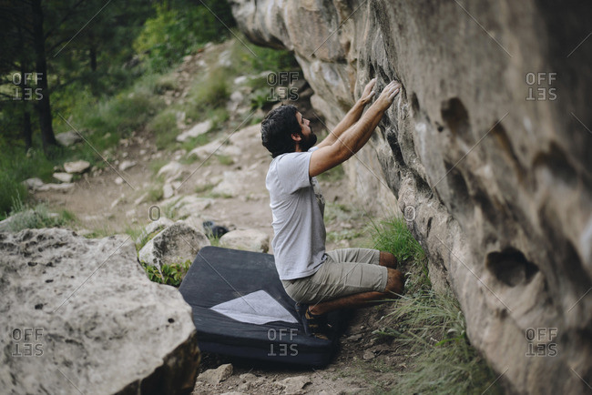 Man crouching on bouldering mat while preparing for rock climbing at forest