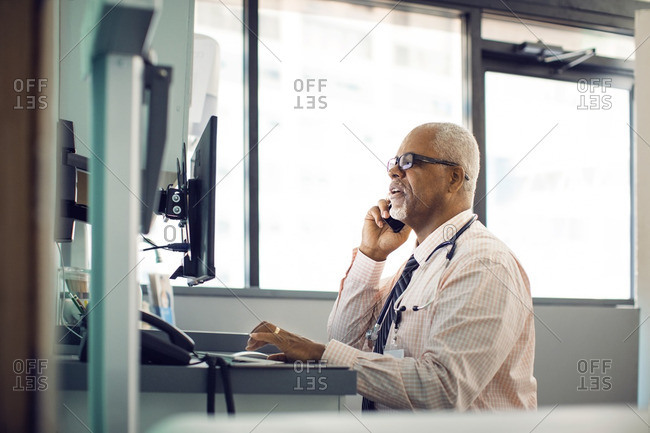 Doctor talking on mobile phone while using desktop computer in hospital