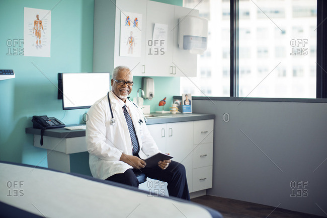 Portrait of confident doctor with tablet computer in clinic