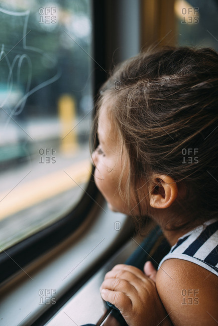 Side view of girl looking through window while traveling in vehicle