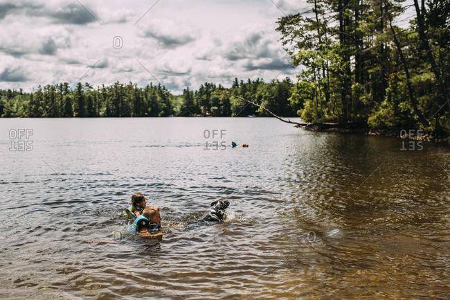 Siblings swimming in lake against cloudy sky