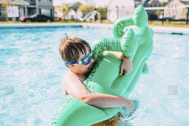 Cheerful boy holding pool raft in swimming pool