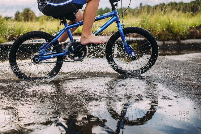 Low section of boy riding bicycle on wet road