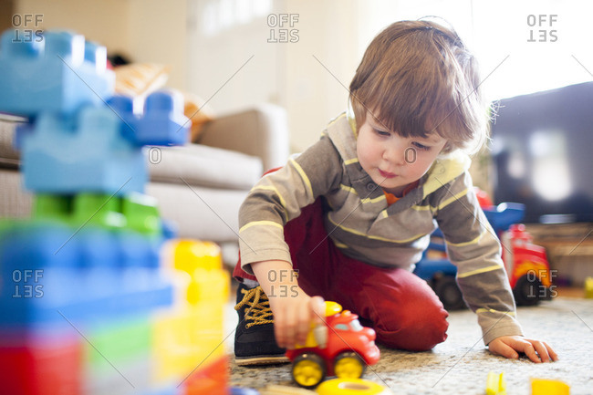 Low angle view of boy playing with toy truck at home