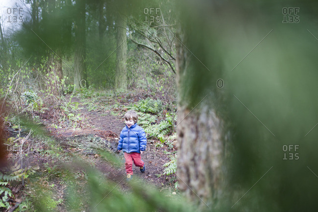 High angle view of happy boy walking in forest