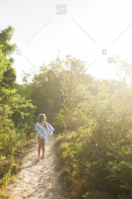 Rear view of girl with towel walking on footpath amidst plants
