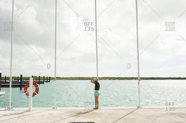 Full length of girl standing on pier by river against cloudy sky