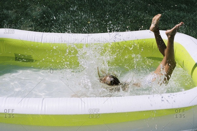 High angle view of girl playing in wading pool