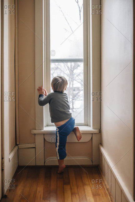 Rear view of curious boy looking through window
