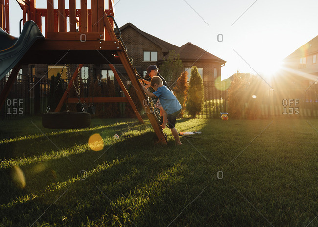Brother playing on slide in backyard during sunset