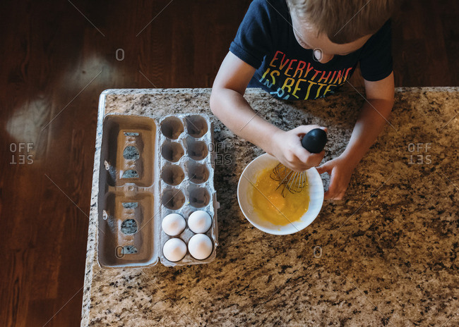 High angle view of boy whisking eggs in kitchen