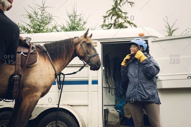Female doctor wearing helmet while standing with horse against ambulance