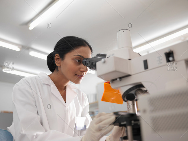 Laboratory technician with microscope - Offset