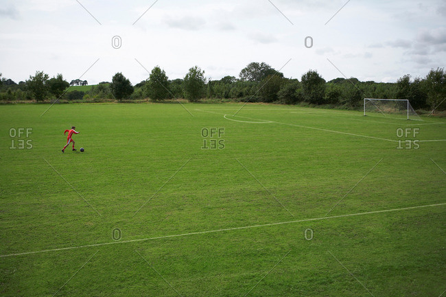 Footballer dribbling a ball towards goal