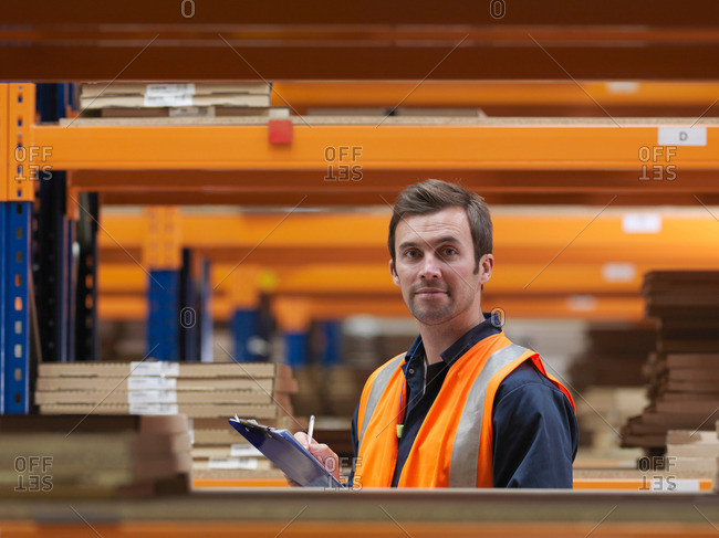 Worker In Aisle Of Warehouse