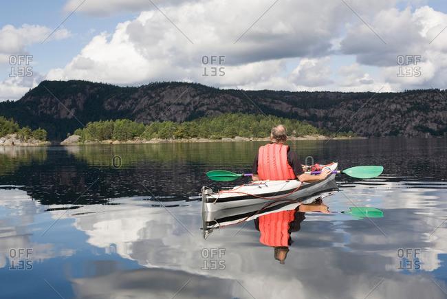 Man kayaking on calm lake