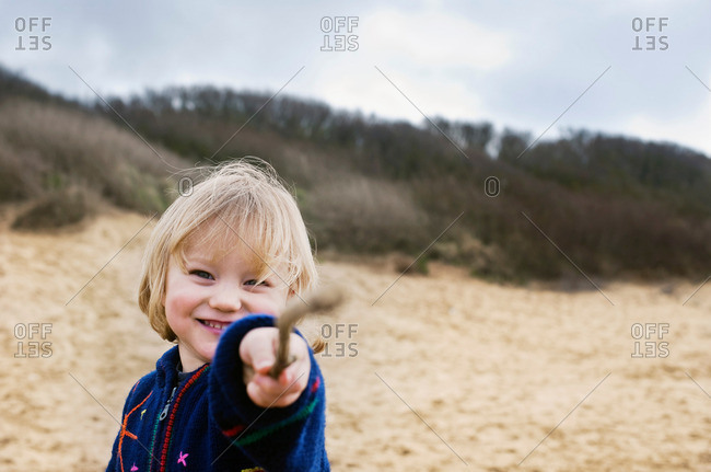 Boy on beach pointing with stick