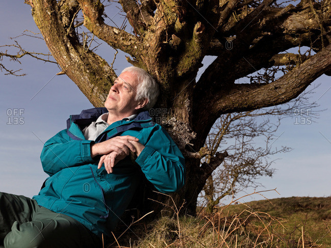 mature man leaning against tree