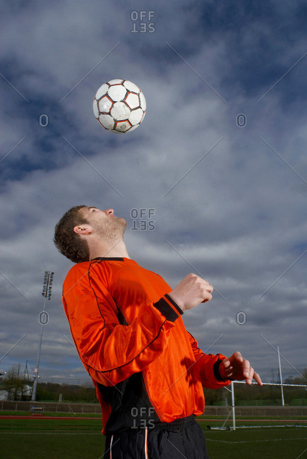 footballer heading a ball to himself
