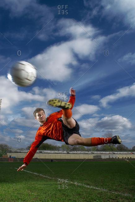 footballer volleying ball mid air