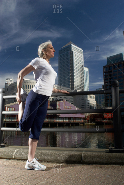 woman stretching by city