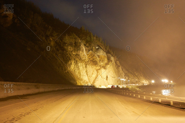 Icy highway and mountain illuminated at night in Alaska