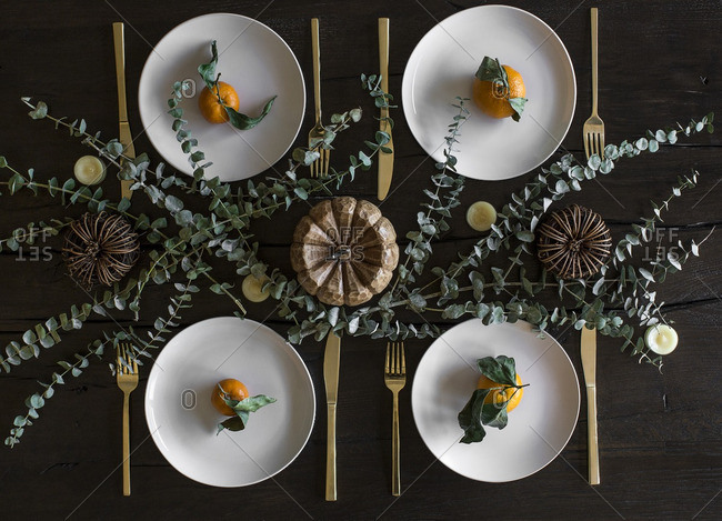 Rustic place settings with clementines, eucalyptus leaves and wooden pumpkins