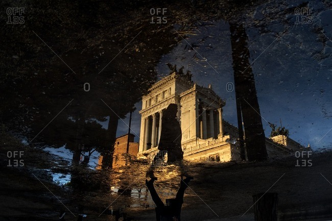 Reflection of a person walking on the street in Piazza Venezia, Rome