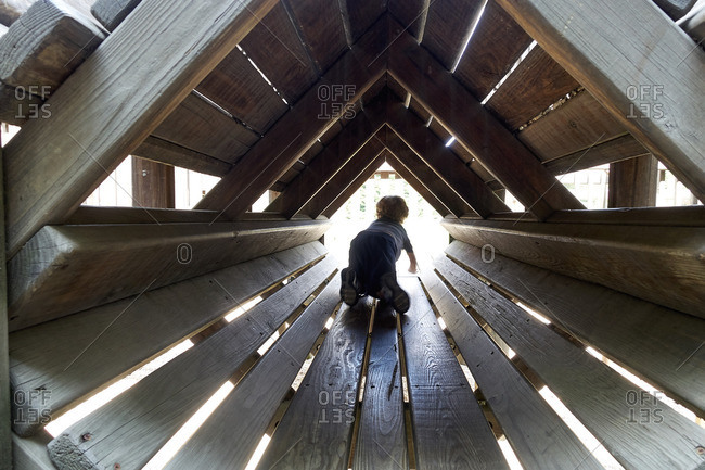 Child crawling in wooden tunnel structure