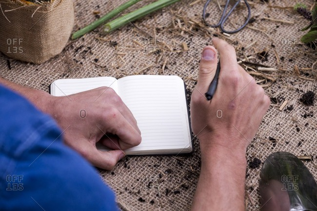 Over shoulder view of gardener writing in notebook