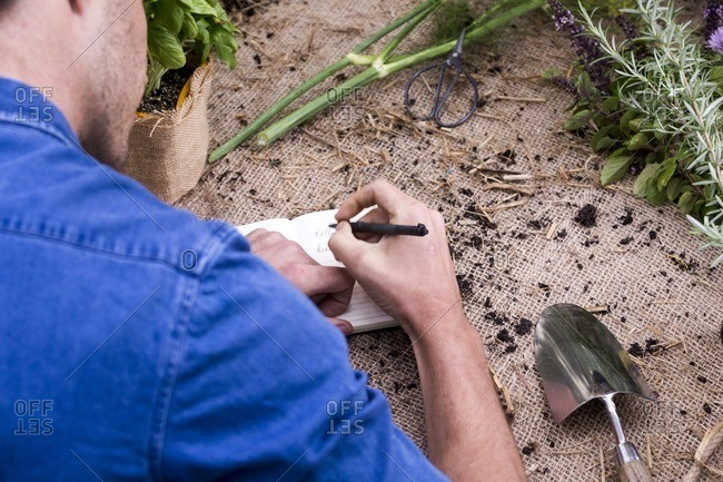 Man writing in notebook on gardening bench