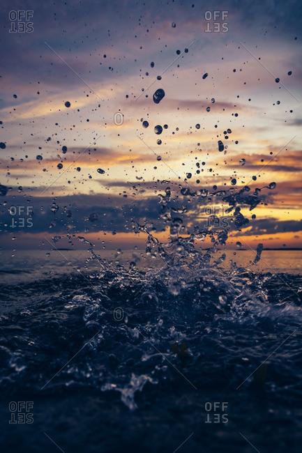 Ocean waves splashing at sunset