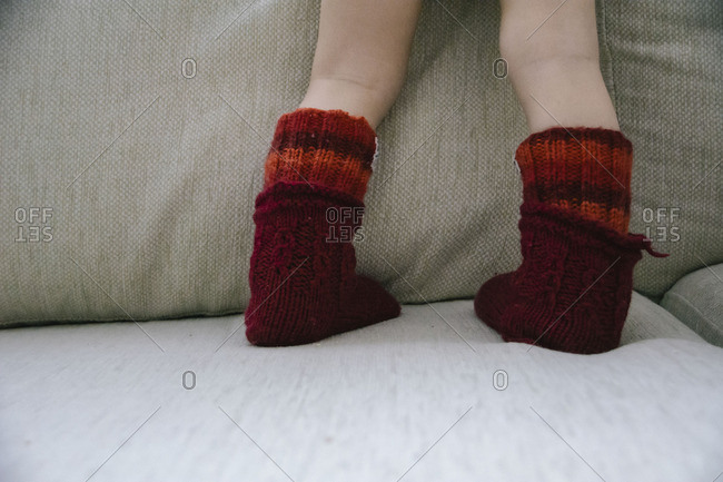 Toddler with red socks standing on couch