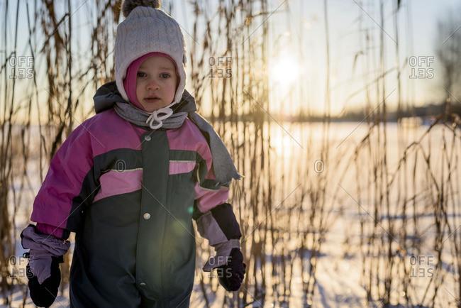 Toddler girl in snowsuit at dusk