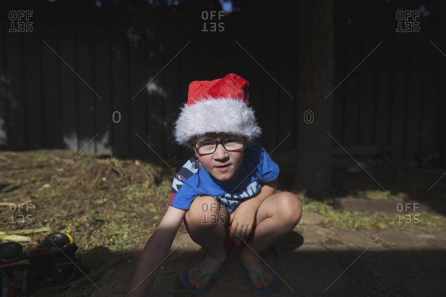 Boy in Santa hat in warm weather clothes