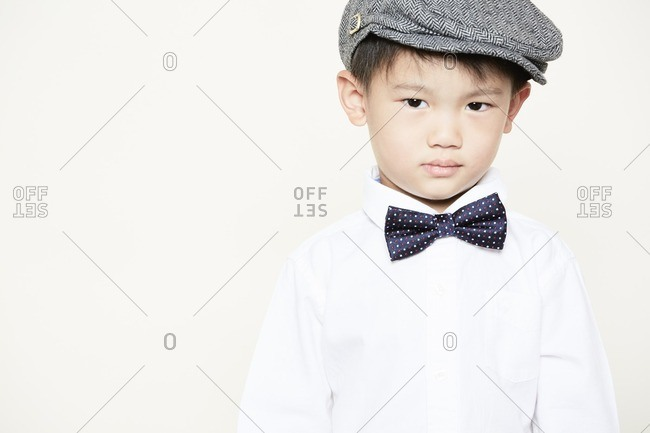 Portrait of boy wearing bow tie and cap