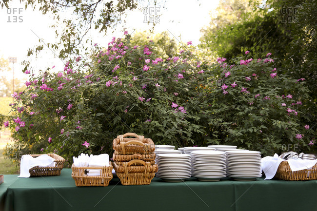 Table outdoors for large dinner with plates and napkins