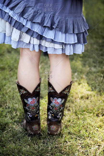 Woman's legs wearing ruffled skirt and cowboy boots