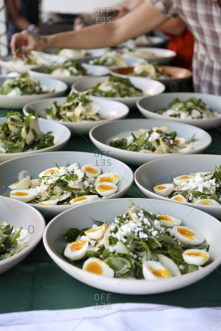 Chef preparing salad with hard boiled eggs for large party outdoors