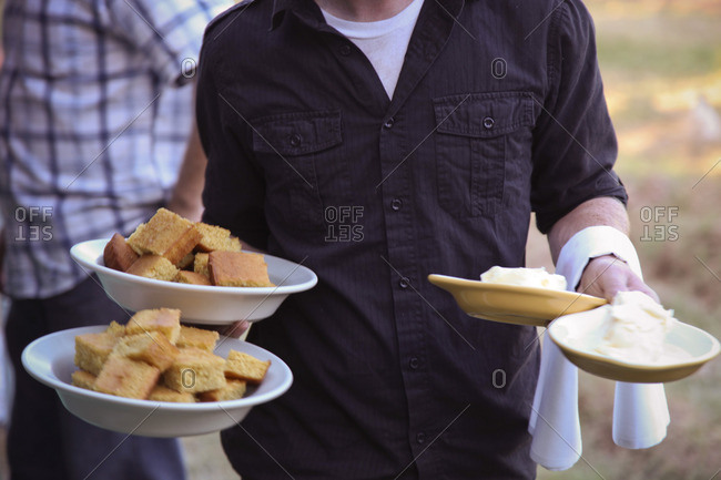 Waiter carrying bowls of cornbread and butter outdoors