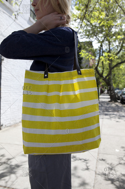 Woman with blond hair holding striped yellow bag on shoulder
