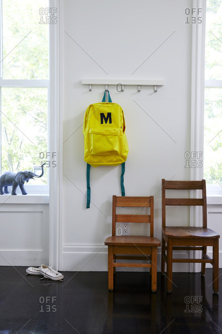 Child's backpack on wall with two wooden chairs